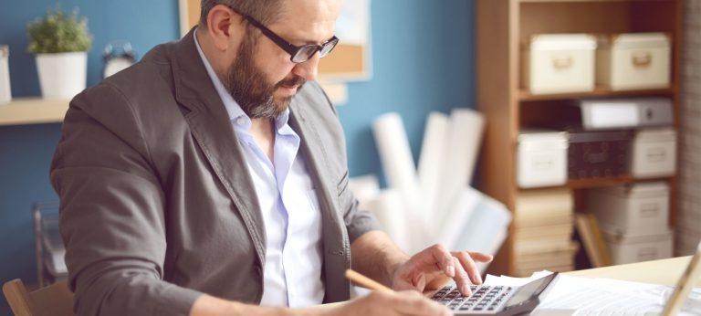 Mann som bruker kalkulator til å gå gjennom dokumenter