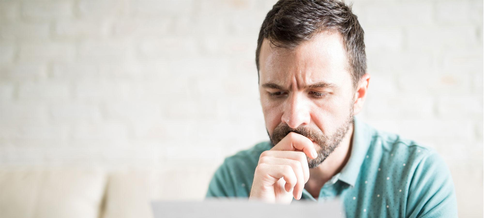 En mann som ser bekymret ut mens han leser et brev