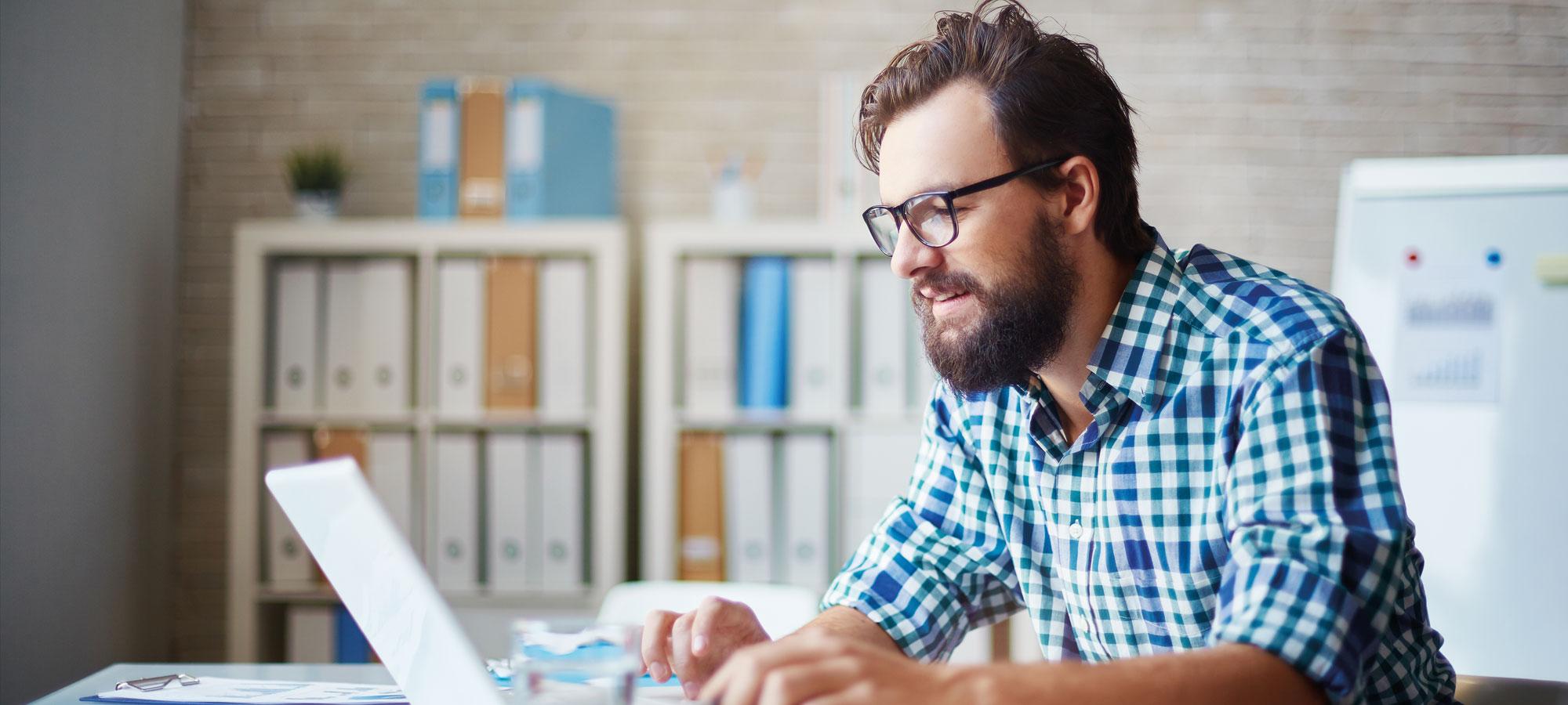 Mann som arbeider på laptop