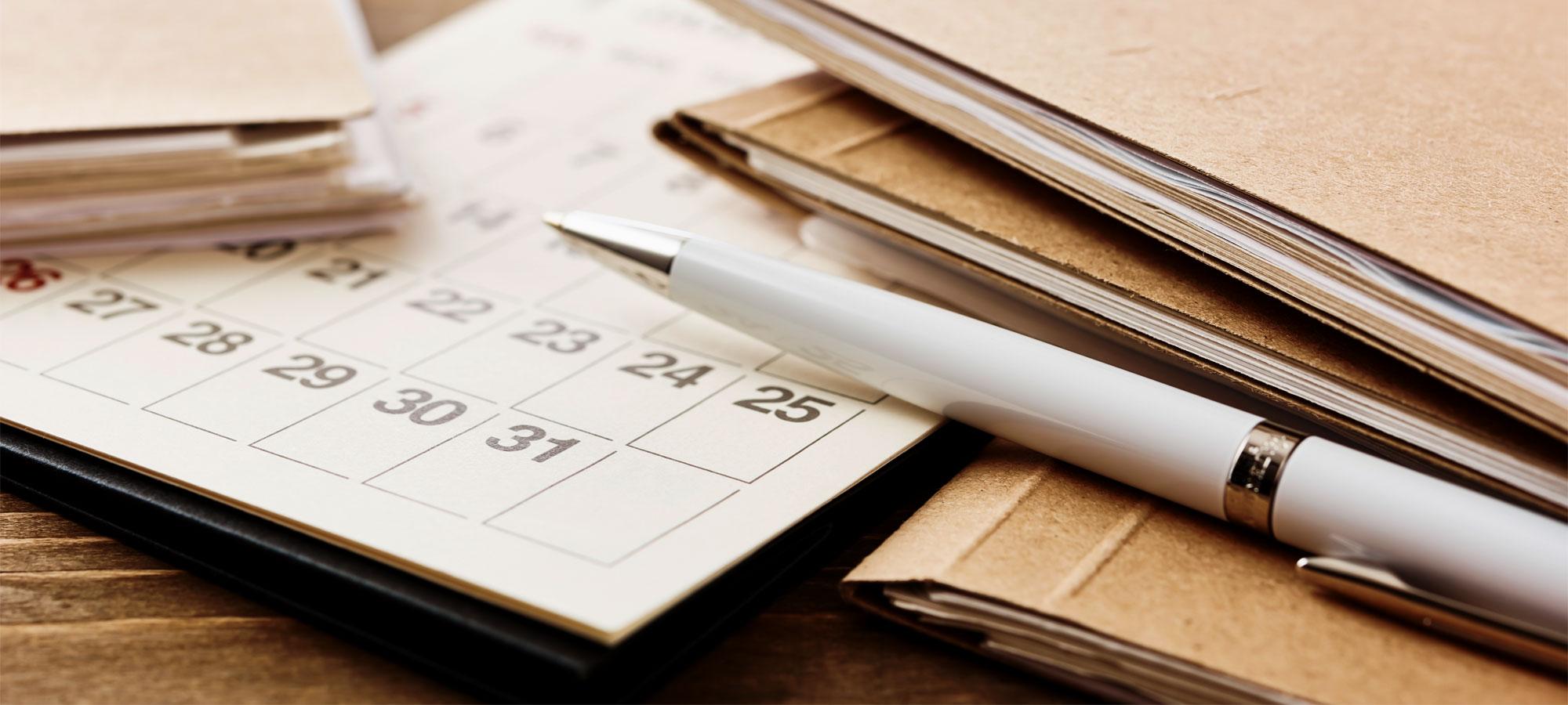 Mapper og en kalender som ligger på et bord