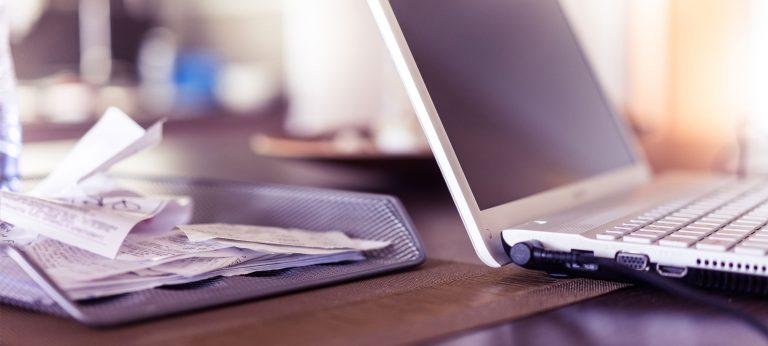 En bunke med bilag ved siden av en laptop
