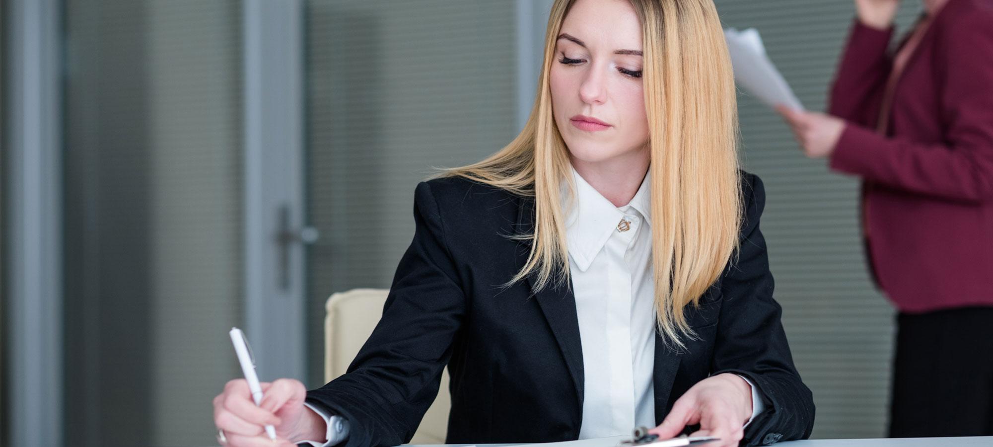 Kvinne som signerer et dokument