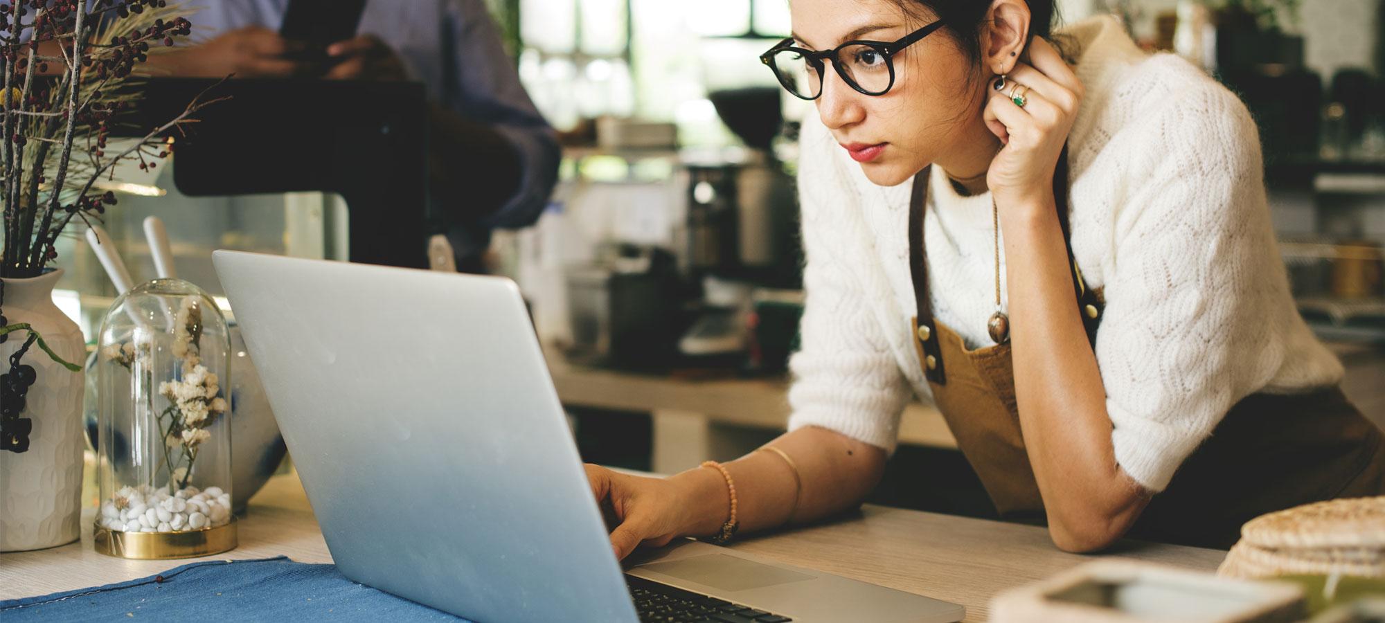 Kvinne som jobber i kafé bruker laptop
